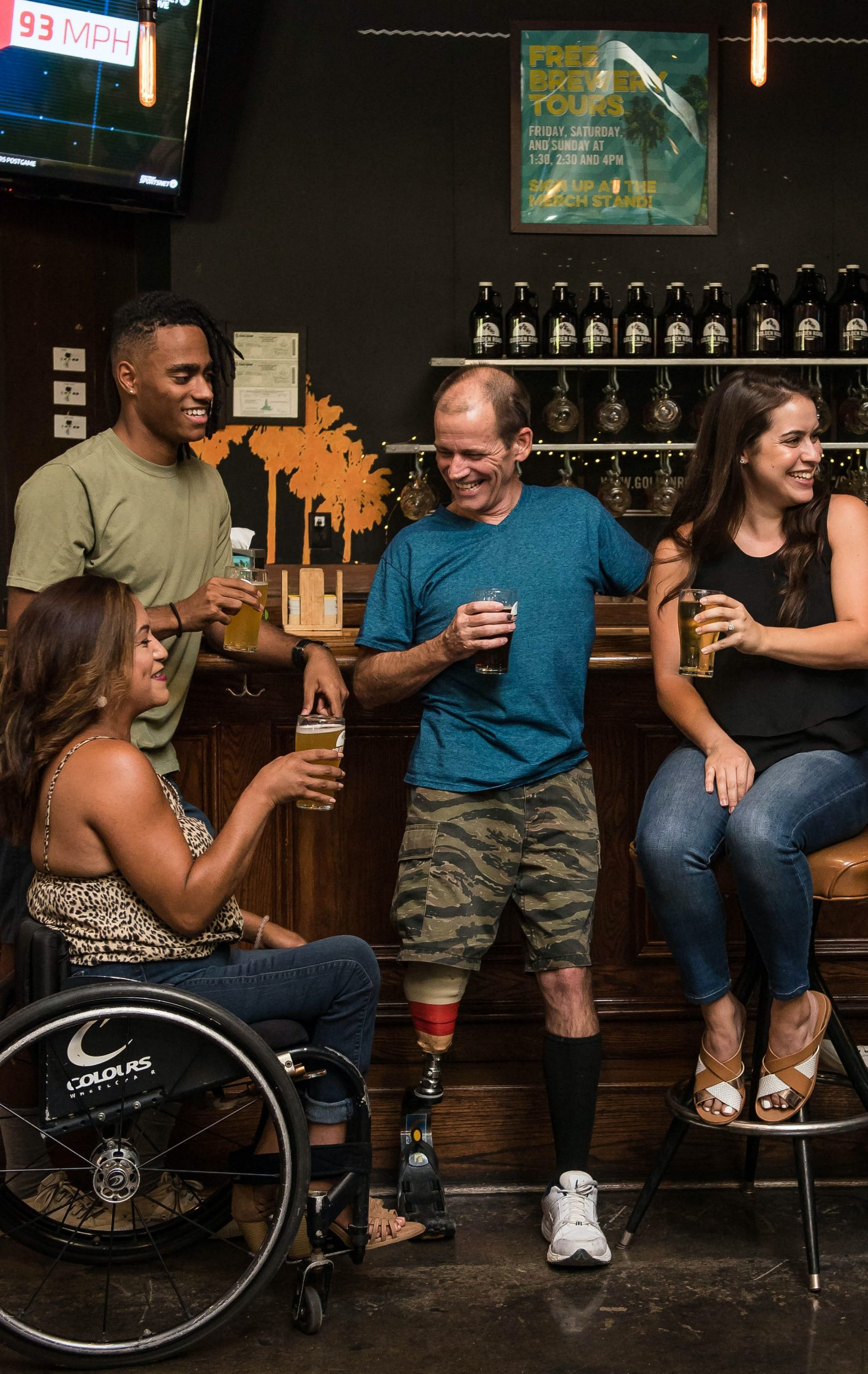 Four people talking at a bar, an African American man standing, a hispanic woman in a wheelchair, a man with an artificial leg leaning against the bar, and a woman sitting on a stool