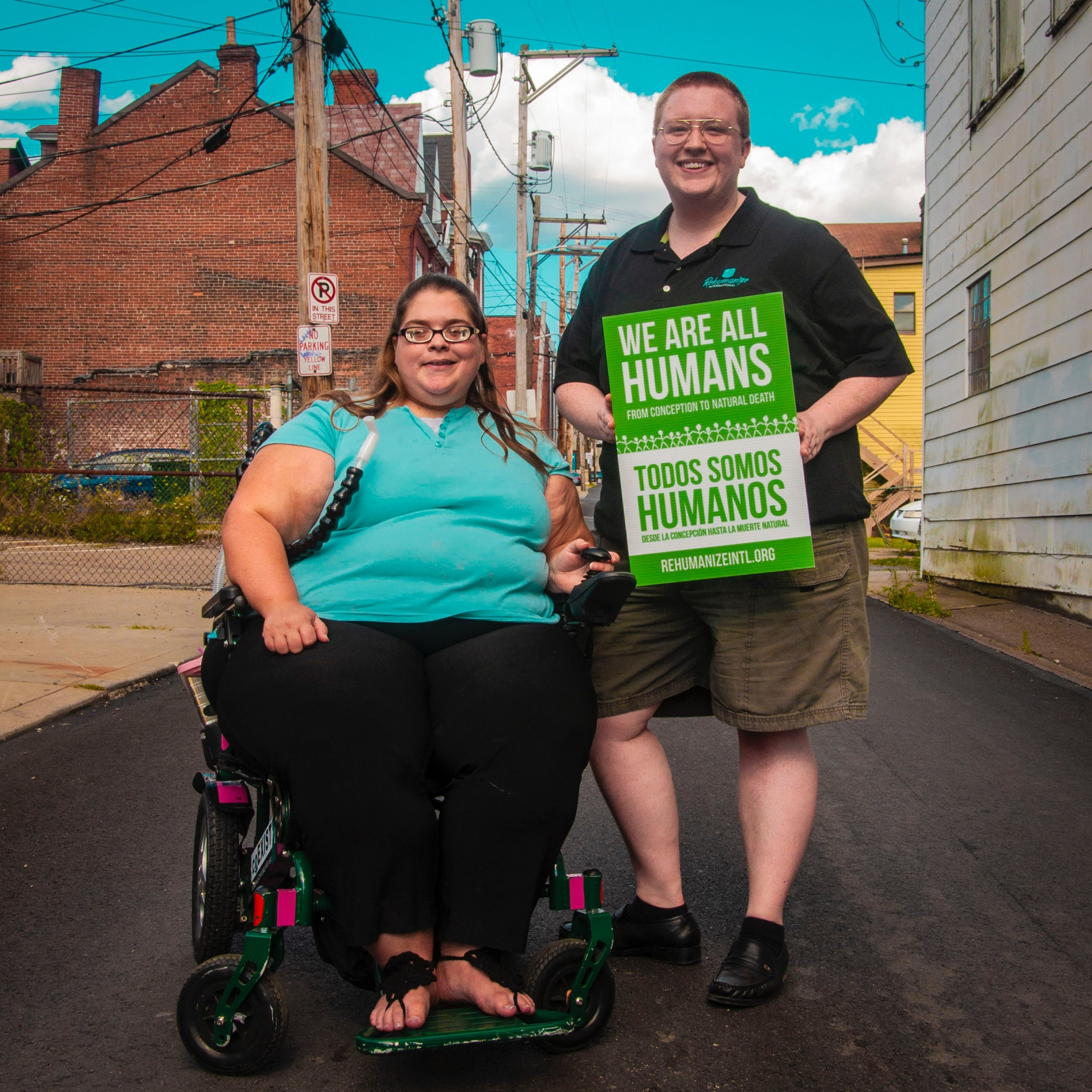 """Woman sitting in wheelchair next to man holding """"We are all human"""" sign"""